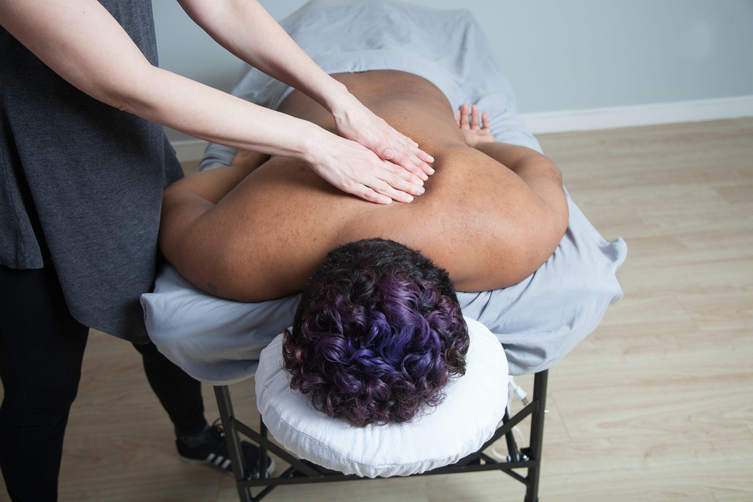 Woman getting back massaged laying down.
