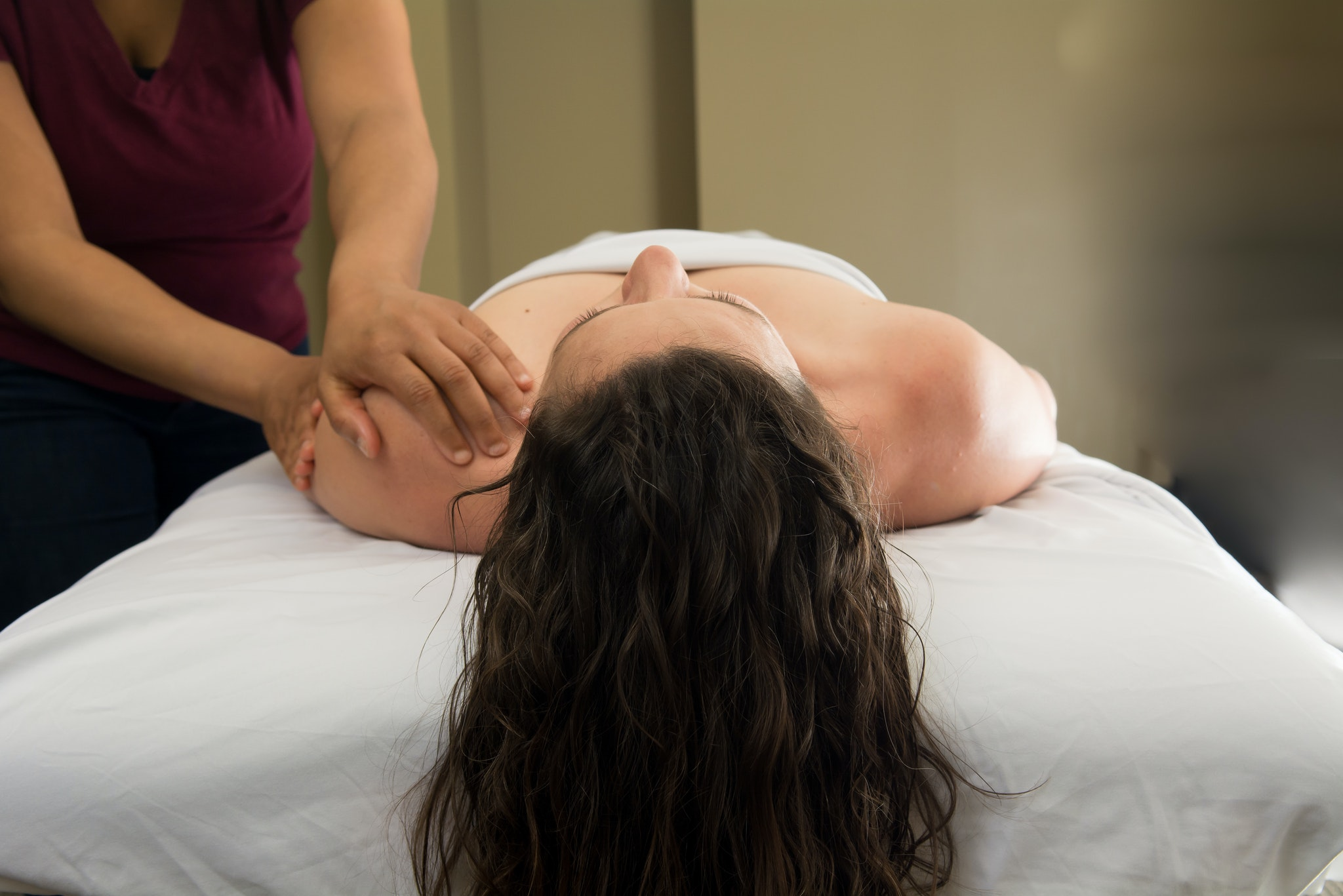 Woman laying on her back getting her shoulder massaged.